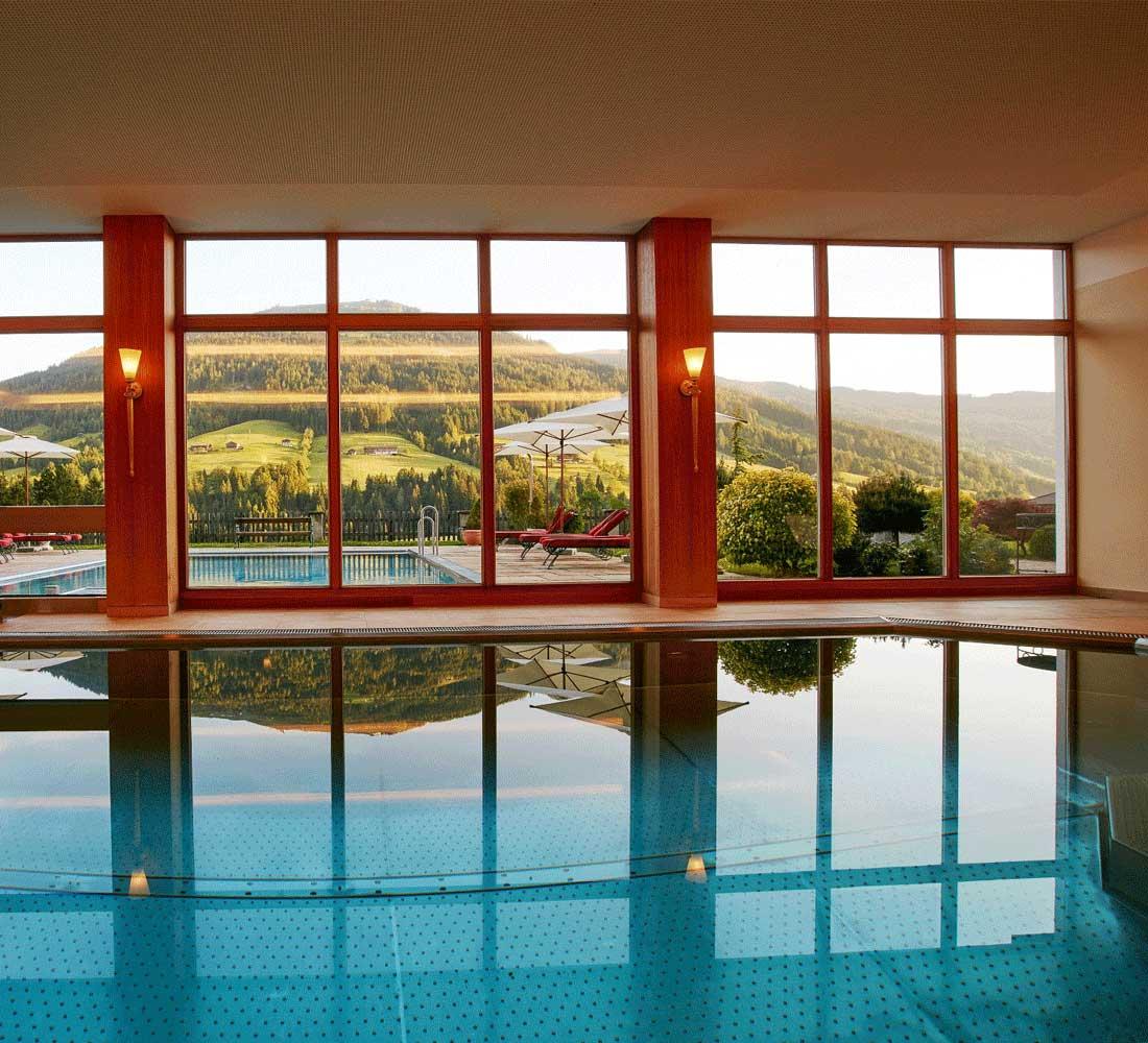 Innenpool mit Panoramaaussicht im Wellnesshotel Tirol Wellnessurlaub Alpbachtal