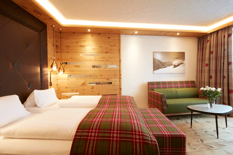 Wohnkomfortzimmer Traumblick Bett und Couch im Wellnesshotel Alpbacherhof in Tirol