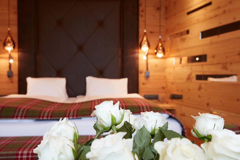 Wohnkomfortzimmer Traumblick Bett mit Rosen im Wellnesshotel Alpbacherhof in Tirol