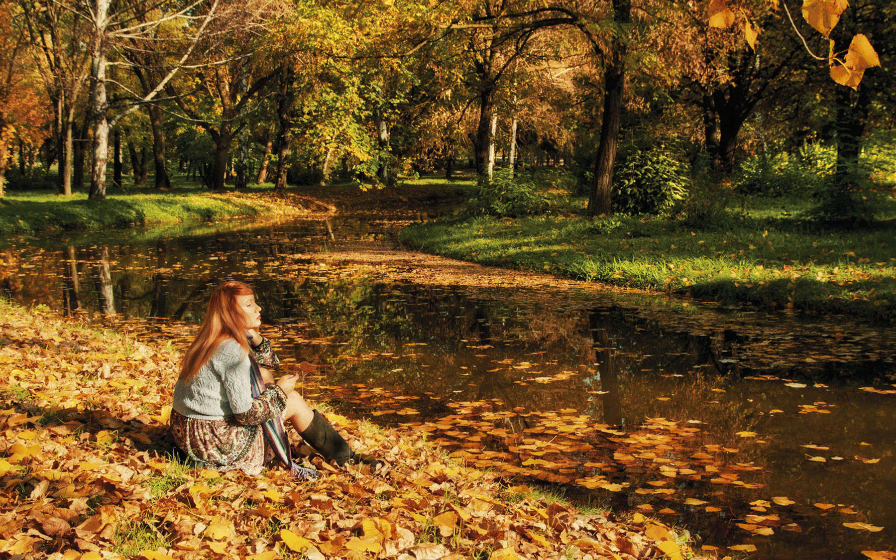 Herbstwald mit Frau an Fluss im Herbsturlaub Tirol