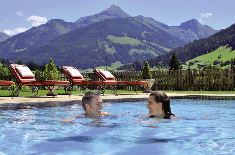Außenpool Paar beim Schwimmen im Naturhotel Alpbachtal