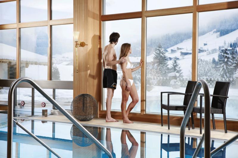 Innenpool Paar blickt in die Winterlandschaft beim Wellness Alpbachtal